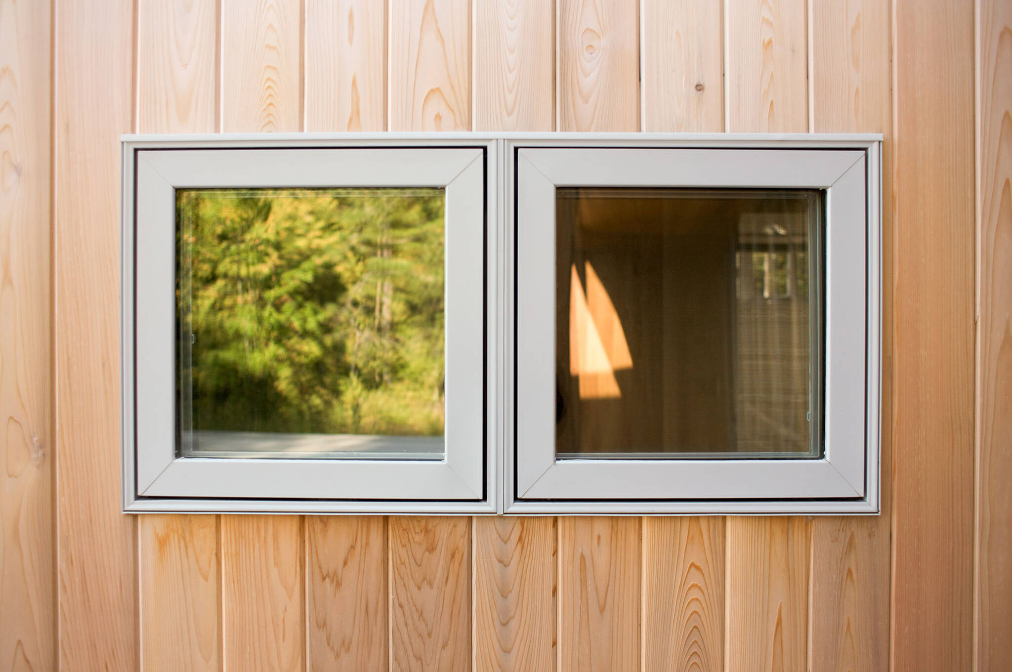 Window detail and vertical cedar siding of the sustainable lake house project in Omena, Michigan designed by the architecture studio Danny Forster & Architecture