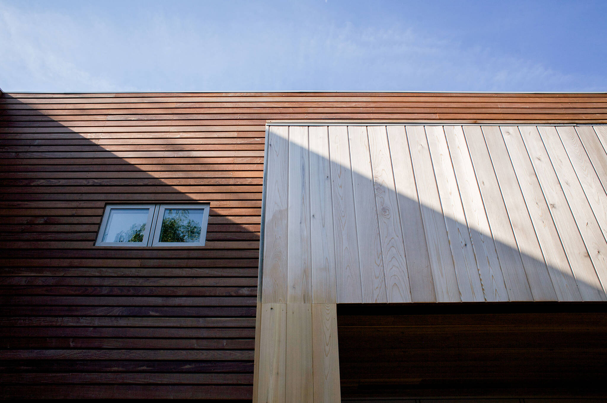 Vertical cedar siding and Horizontal IPE Brazilian walnut rainscreen cladding of the sustainable lake house project in Omena, Michigan designed by the architecture studio Danny Forster & Architecture