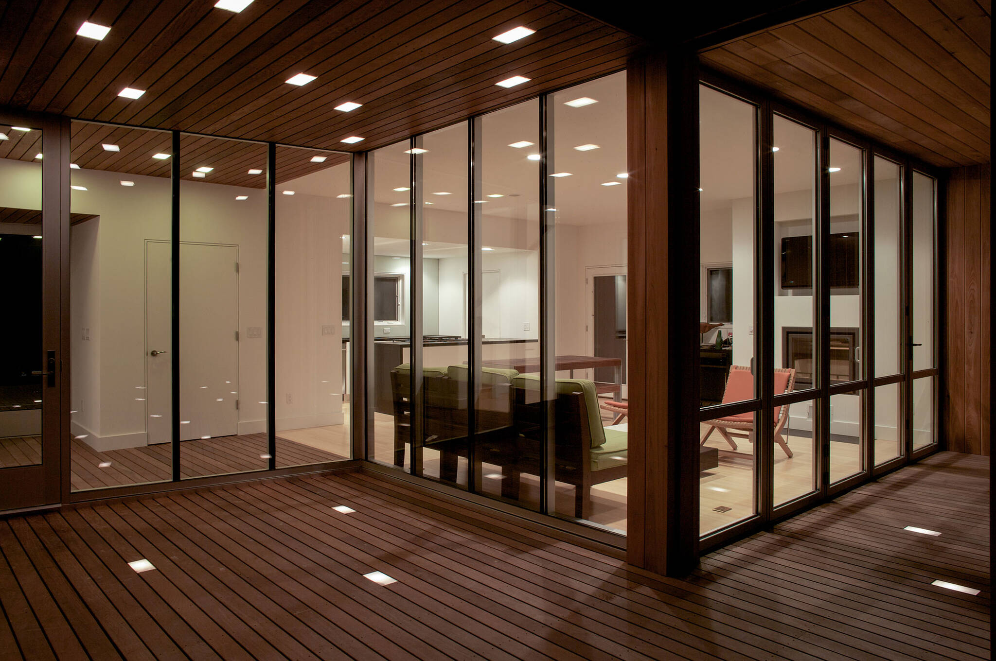Night view of the wooden deck and framed windows of the sustainable lake house project in Omena, Michigan designed by the architecture studio Danny Forster & Architecture