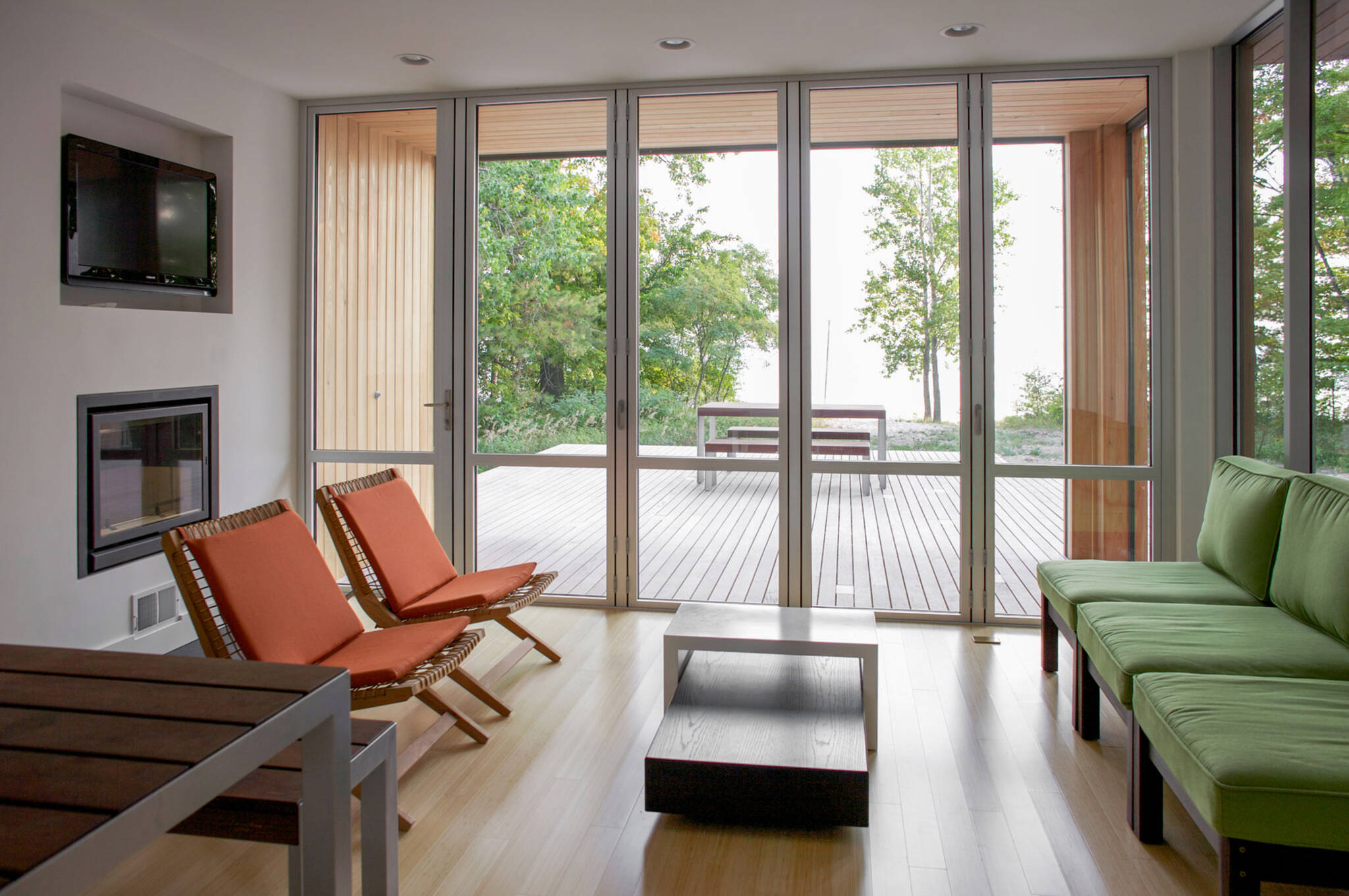 Living room folding doors sequence of the sustainable lake house project in Omena, Michigan designed by the architecture studio Danny Forster & Architecture