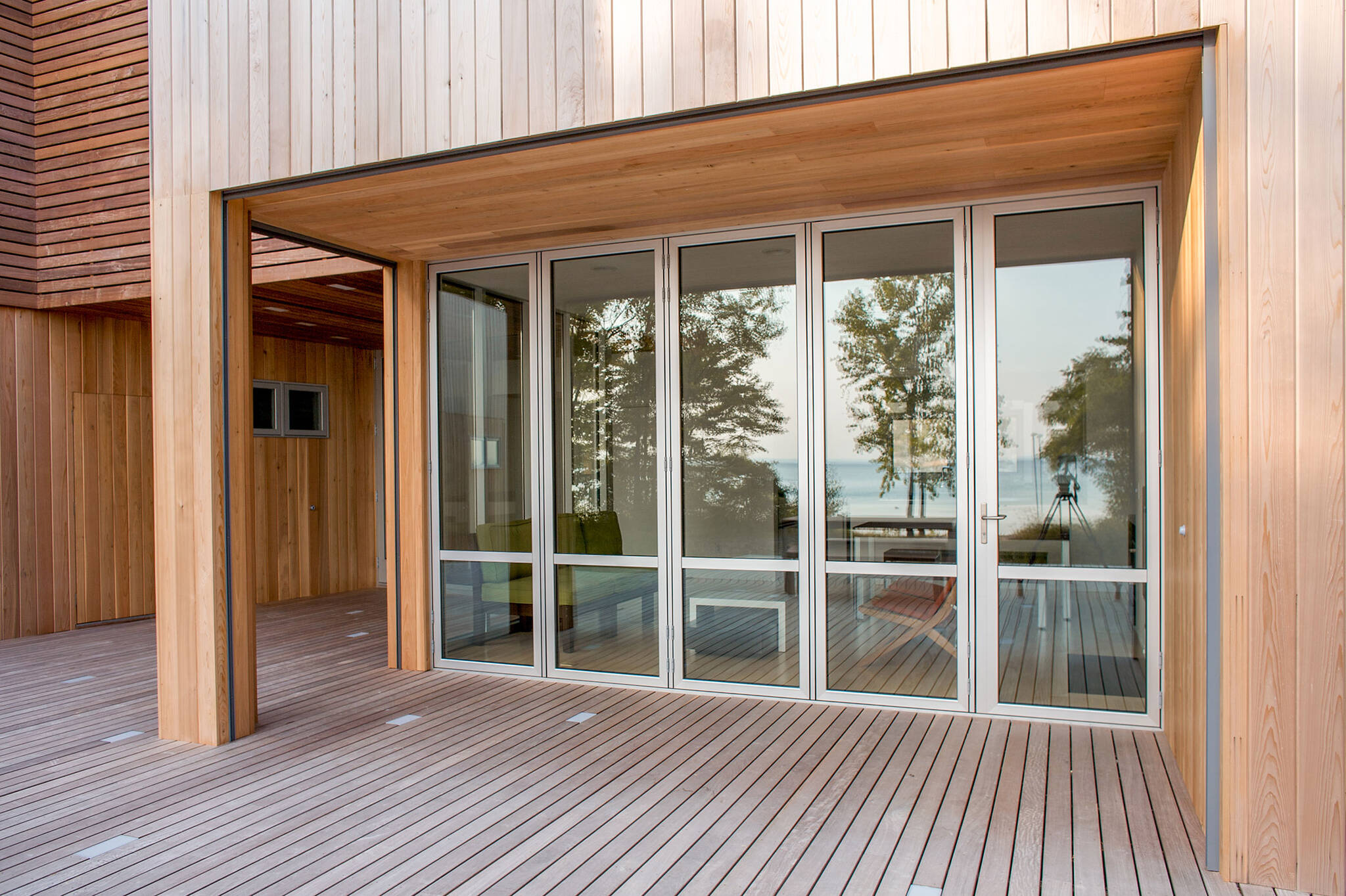 Deck folding doors sequence of the sustainable lake house project in Omena, Michigan designed by the architecture studio Danny Forster & Architecture