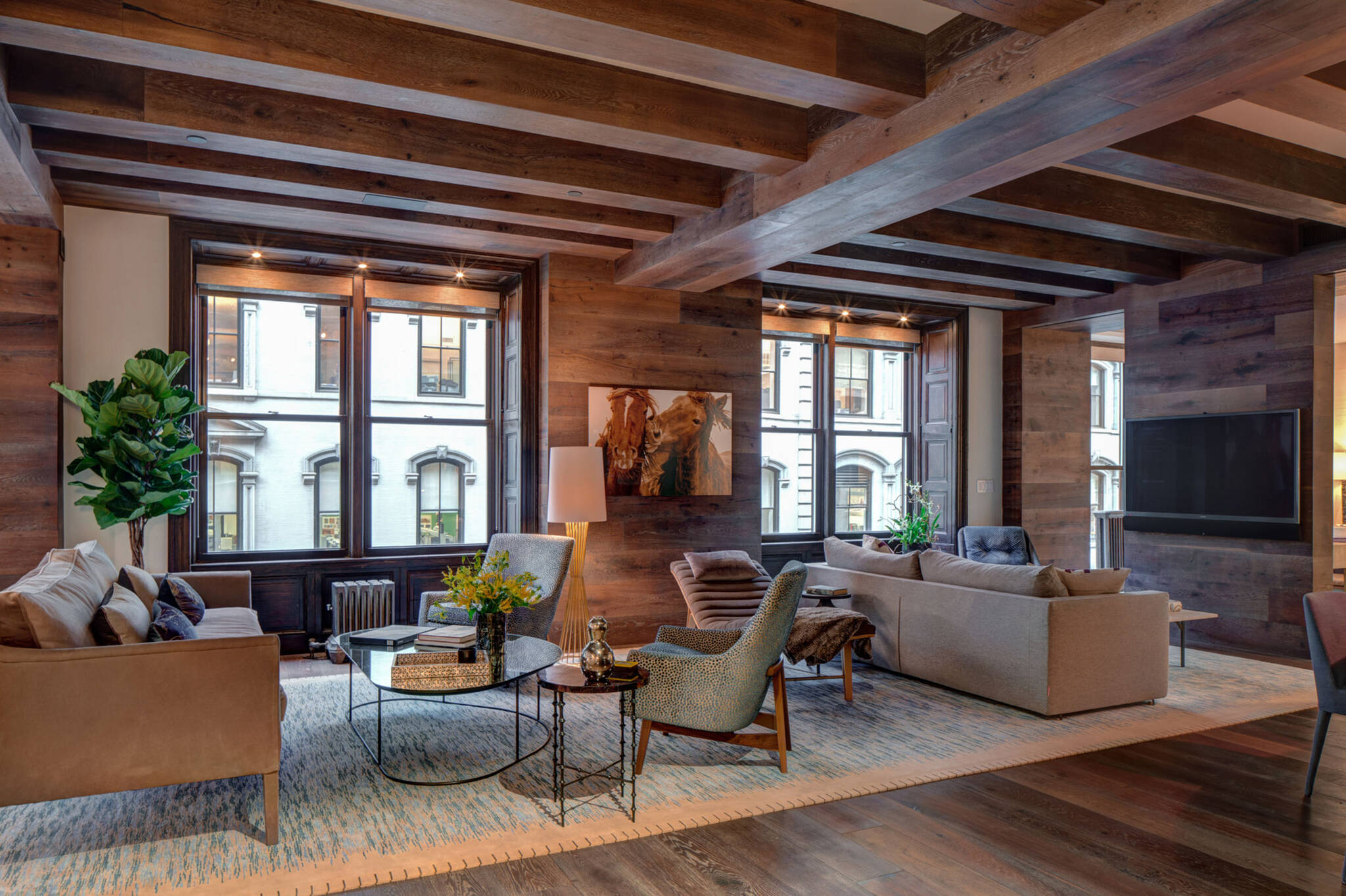 Living room under the wooden beam and cross beams ceiling of the loft renovation project in Union Square, New York City designed by the architecture studio Danny Forster & Architecture