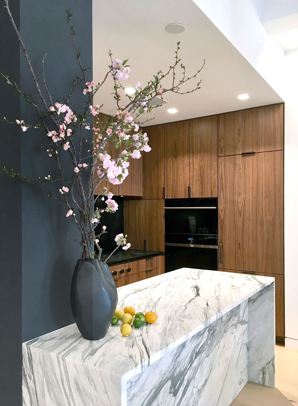 Dark walnut cabinetry and marble island textures on the kitchen of the Loft renovation project in Chelsea, New York City designed by the architecture studio Danny Forster & Architecture